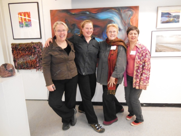 "Arlington singer Louise Grasmere, former ACA Communications Assistant Lindsey Schust, Member Artist Grace Schust, and ACA Studio Artist Connie Chamberlain, in front of Grace Schust's new painting, ""Surfacing."""