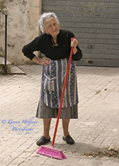 Elderly Sicilian woman pausing from sweeping, holding her broom.